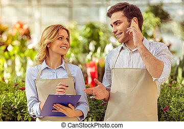 People in orangery - Young woman and man in aprons in...