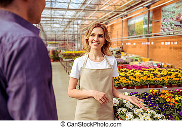 People in orangery - Beautiful young woman in apron is...