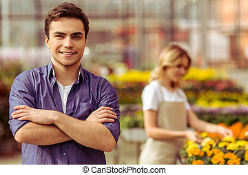 People in orangery - Handsome young man in casual clothes is...