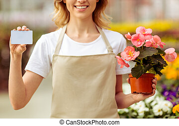 Woman in orangery - Beautiful young woman in apron is...