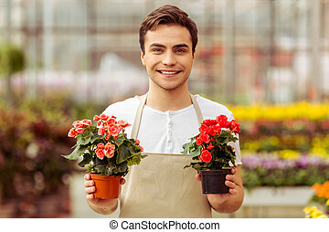 Man in orangery - Handsome young man in apron is holding...