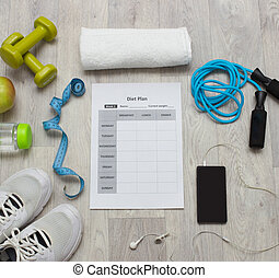 Various sport equipment with diet plan on wooden background...