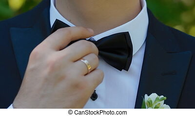 Groom straightens his tie - Groom straightens his bow tie...