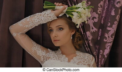 Beautiful caucasian bride pose near the window with wedding...