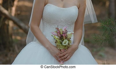 Bride hold wedding bouquet of white and pink calla near the...