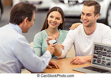 People in motor show - Young couple is smiling while buying...