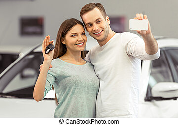Couple buying a car - Beautiful young couple is smiling and...
