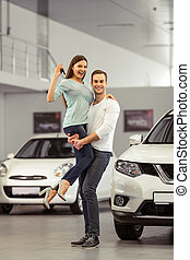 Couple buying a car - Beautiful young couple is smiling,...