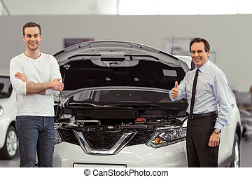 People in motor show - Handsome middle aged salesman is...