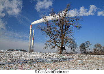 Deer stand in winter with smoking chimney of power plant...