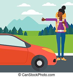 Young woman hitchhiking - An african-american woman...