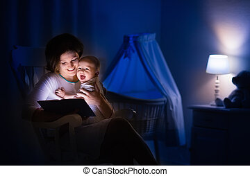 Mother reading a book to little baby - Mother and baby...