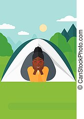 Woman lying in tent. - An african-american woman crawling...
