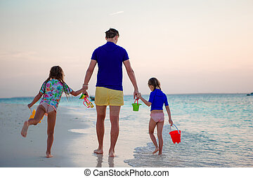 Happy family in sunset on the beach