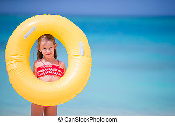 Adorable little girl with inflatable rubber circle during...