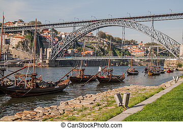 boats on douro river with a bridge in the background