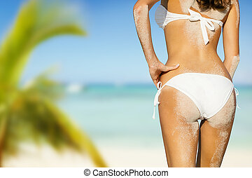 Young woman in bikini looking at beach with sand on her...