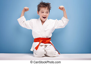 Boy in karate costume. - Little boy with orange belt on...
