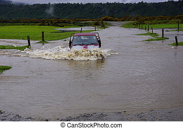 through the floods - Farmer crosses a flooded creek in his...