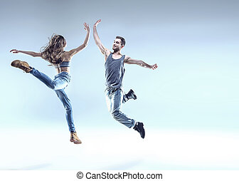 Two young dancers in a jumping pose - Two young breakdancers...