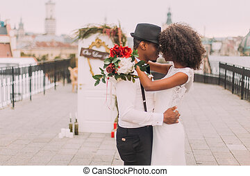 Happy black wedding couple softly hugging on the rooftop...