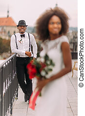 Stylish black groom in focus and his charming bride on the...