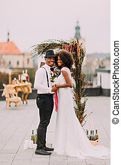 Gorgeous black wedding couple holding hands and smiling on...