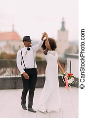 Happy newly wed black couple gracefully dances on the...