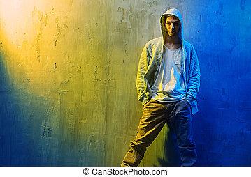Handsome hi hop dancer leaning on a concrete wall - Handsome...