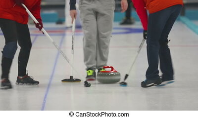 Curling stone slide, players sweeping - Players sweeping and...