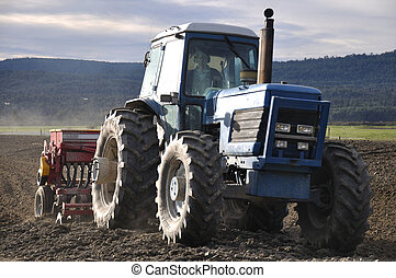 sow the seed - Farmer drilling seed into pasture paddock,...