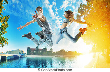 Two jumping dancers on an urban background - Two cheerful...