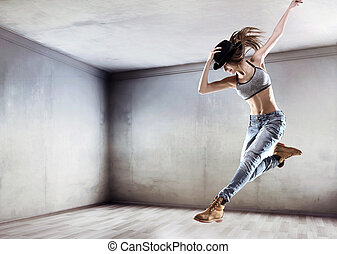 Athletic dancer jumping on a concrete wall background -...