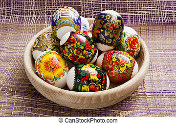 Easter eggs in a wooden plate on a purple background