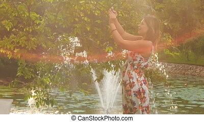 Backlight Side View Blond Girl Makes Selfie in Park by Fountain