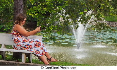 Blond Girl Sits on Bench at Fountain Touches Iphone in Park...