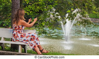Blond Girl Sits on Bench Takes Photo of Fountain with Iphone...