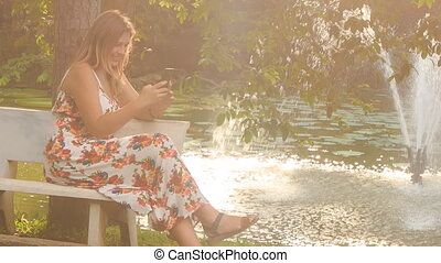 Backlight Blond Girl Sits on Bench at Fountain Plays Iphone...