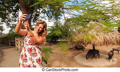 Blond Girl Makes Selfie against Antelopes in Zoo Open Air...