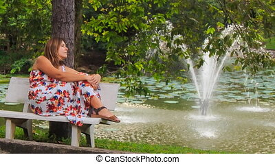 Blond Girl Sits on Bench Looks at Fountain in Park