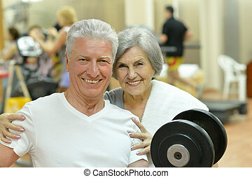 Senior couple exercising in gym - Portrait of a senior...