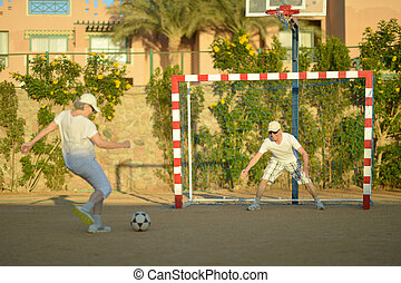 Active couple playng football - Portrait of active senior...