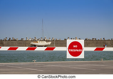 Stop red sign on barrier in a harbour