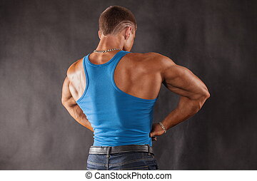 Bodybuilder in jeans and a blue t-shirt