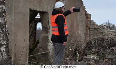Engineer filmed with tablet PC near to abandoned, destroyed...