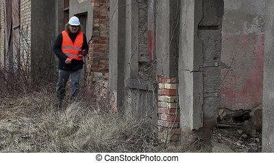 Engineer with tablet PC near to the abandoned, destroyed...