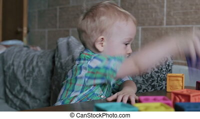 Boy plays with toy blocks at home
