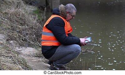 Environmental inspector checks the river pollution