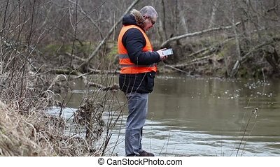 Environmental inspector checks the river pollution in early...