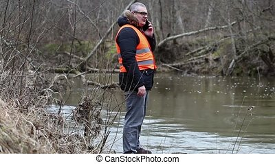 Environmental inspector with smartphone near the river